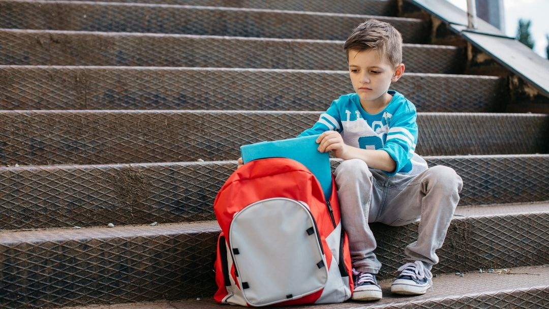 student in trouble at school - little boy on school steps with red backpack