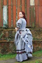 Photo: Vestido vitoriano em tricoline listrado comporto por casaca, saia e sobressaia com babados, aplicação de renda guipure e fitas.  A partir de R$ 600,00.  Underwear: bloomer e chemise, corset 1880, bustle e pettitcoat.