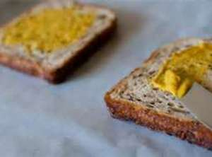 Spread bread with mustard, cut into bite size squares. Lay in buttered crockpot. Layer sausage. Then...
