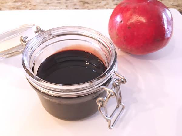 A Jar With Molasses In It Sitting On A White Table Mat With A Pomegranate Next To It.