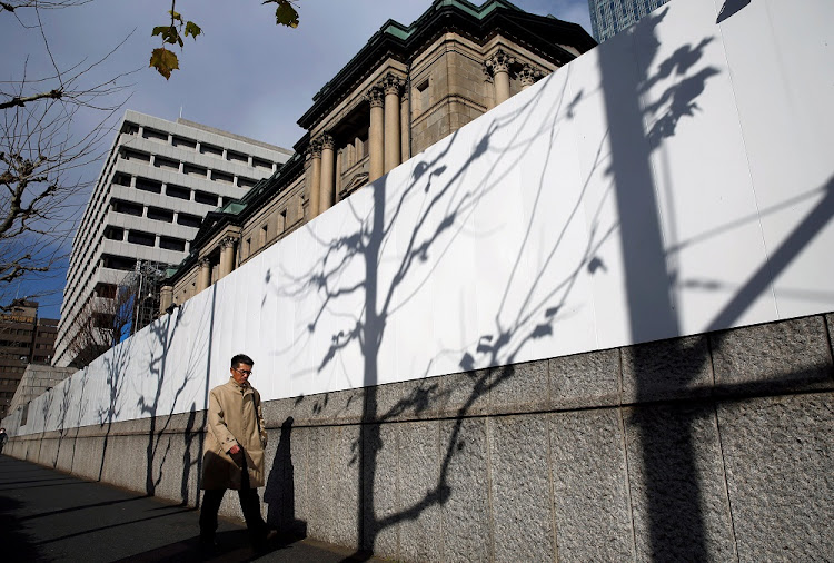 Easing: A man walks past the Bank of Japan building in Tokyo. Central banks such as the Bank of Japan continue to run quantitative-easing programmes, while the US recently cut its corporate tax rate. Picture: REUTERS
