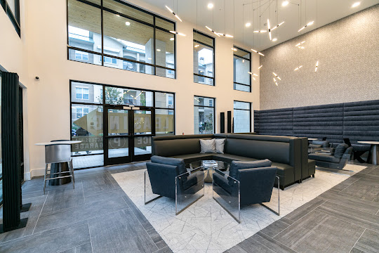 Gorgeous community clubhouse seating area with modern hanging light fixtures and black accents