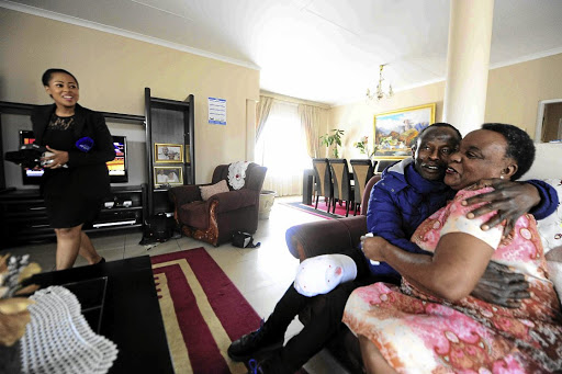 Cyril Ramaphosa's sister Ivy embraces Herbert Sithole, a family friend, after Cyril was elected as the new president of South Africa yesterday. / Thulani Mbele