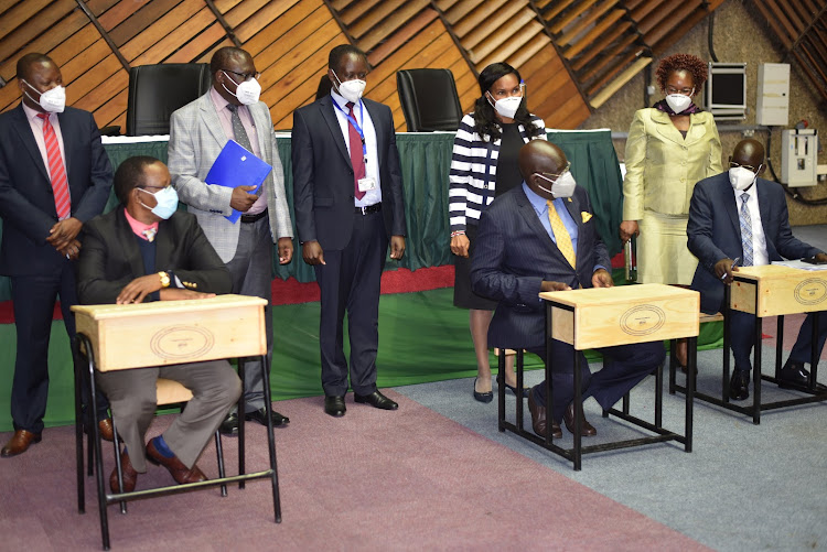 Education Cabinet Secretary George Magoha (sitting centre) with a group of legislators sample locally made desks for secondary schools.
