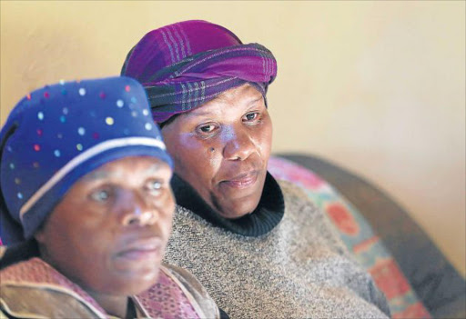 DEVASTATED: Widow Nosipho Kondlo, far right, in tears seen here with her sister Nosipho Gusha after she was prevented from attending the funeral of her 84-year-old husband, Bonisile Kondlo