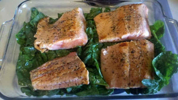 When salmon is browned, lay salmon on top of spinach in the baking dish....