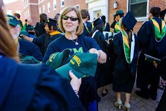 Photo: Alumni volunteers present new graduates with a McDaniel cap.