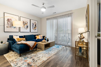 Model living room with wood-inspired flooring, light walls, deep blue couch, and neutral rug