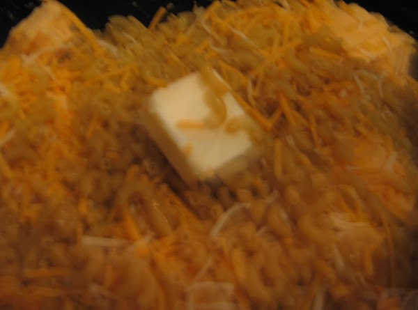 Spray inside of Crockpot with non-stick cooking spray. Combine uncooked pasta,cheeses, garlic,pepper and butter.