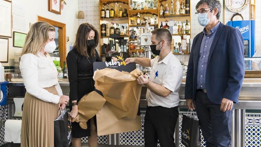 María Luisa Cruz, Manuel Cortés y Carmen Belén López entregando material promocional en Adra.