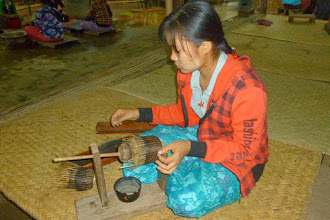 Photo: This young lady is weaving horse hair around the bamboo strips which makes the finished lacquer product more flexible.