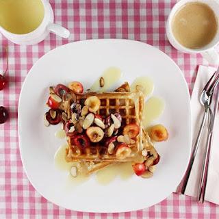 Yogurt and Oat Waffles with Fresh Cherries and White Chocolate Sauce.