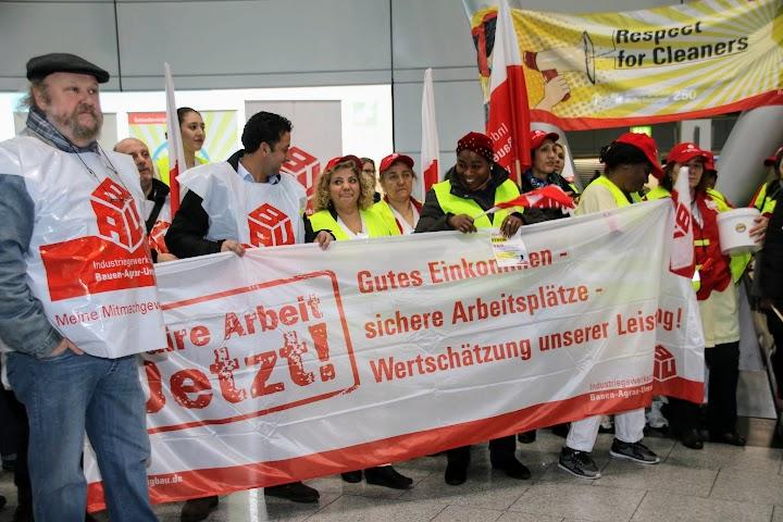 Streikende mit IG-BAU-Westen, Transparente: «Respect for Cleaners» und «Gutes Einkommen – sichere Arbeitsplätze – Wertschätzung unserer Leistung!».