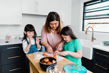 To explore new things offline, a mother and her two young daughters chop a red pepper in the kitchen.