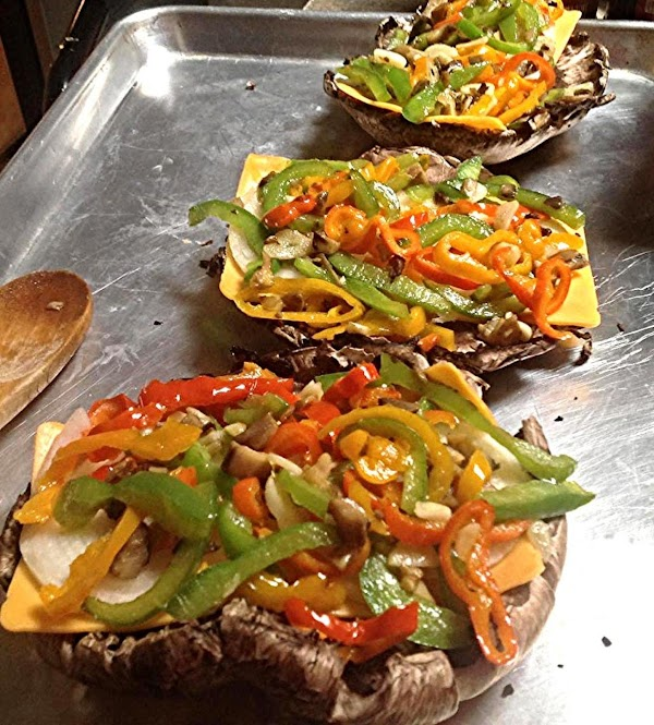 Top each mushroom cap with an even amount of sauteed peppers. Then top each...