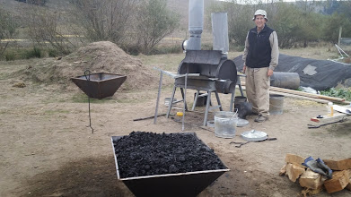 Photo: Paul Anderson's C-4 kiln. Biochar made during the School by the C-4 is shown piled in the pyramid.