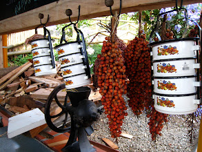 "Photo: These red berries are called ""carosos"" and require a rock or nutcracker to open. Beside them are traditional cooking dishes that can be put directly into the oven or over a flame."