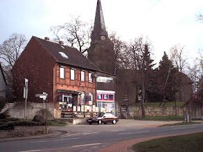 Photo: 2003 - Das Geschäft von Richard Graß an der Hauptstraße, im Hintergrund die St.Petri Kirche