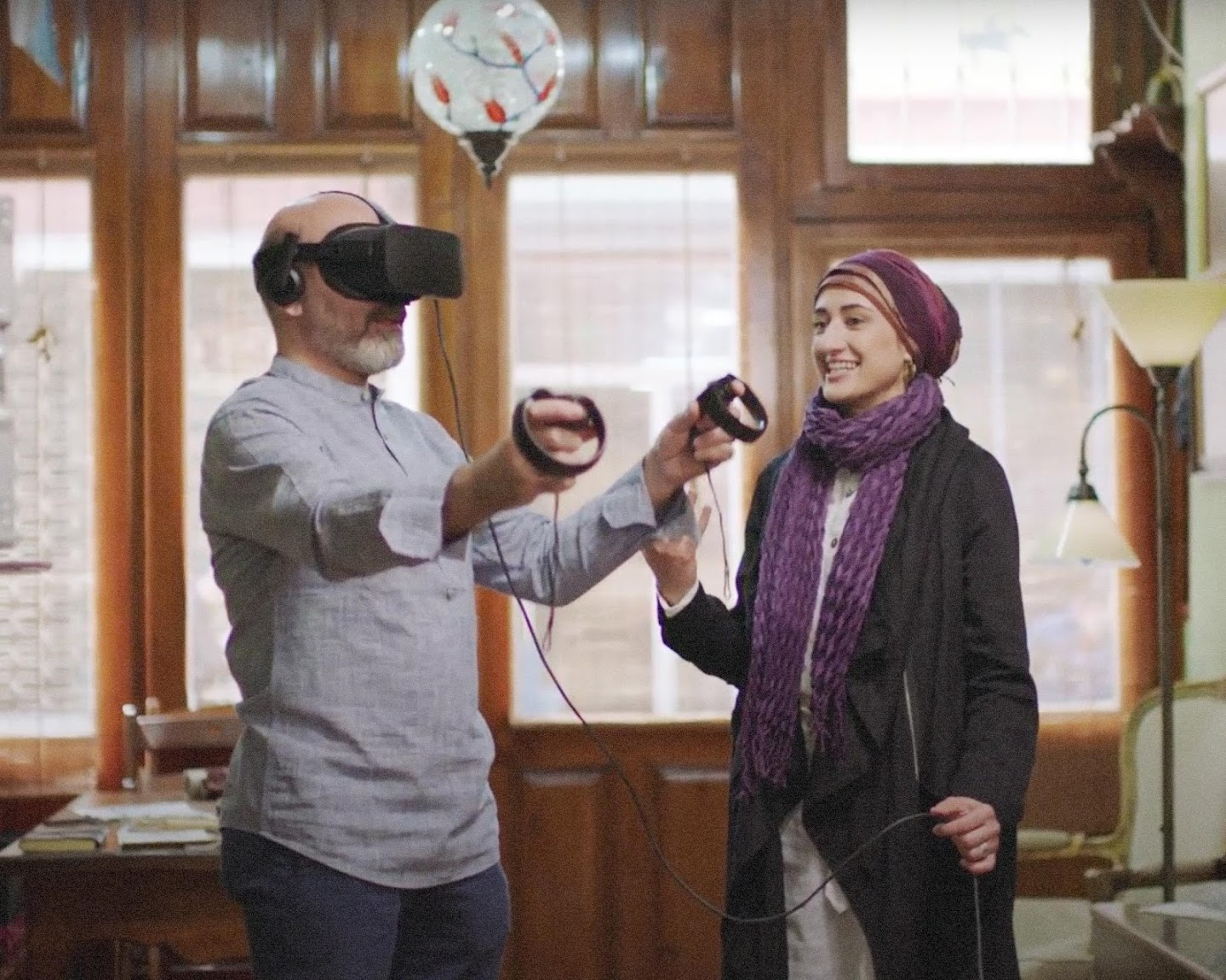 Efdaluddin wearing VR headset to view Soraya's calligraphy message in 3D