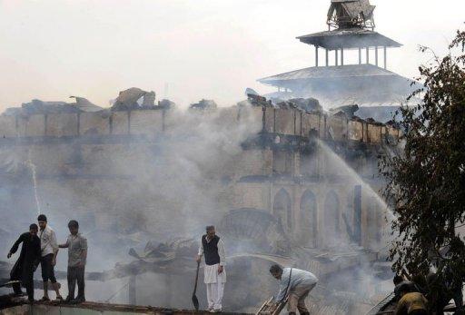 Photo: Des habitants aident les pompiers à éteindre l'incendie qui ravage le temple soufi Dastageer Sahib à Srinagar, au Cachemire. (© 2012 AFP)