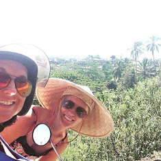 women travel together around bali on a scooter bike, one wears a Vietnamese hat