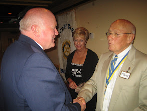 Photo: District Governor Bill  Griffin congratulations President Blaine Timmer. First Lady Nancy Timmer looks on.