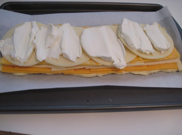 Layer the cheeses. Slice the cream cheese and spread over the top.  Pour...