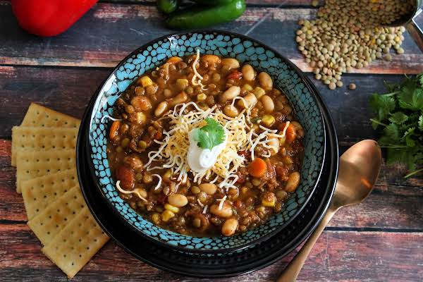 A Bowl Of Lentil Chili With Sour Cream And Cheese.
