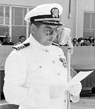 Photo: Capt. G.H. Duffy reads his orders at the change of commands cermonies where he was relieved by CDR F.O. Green as commanding officer.