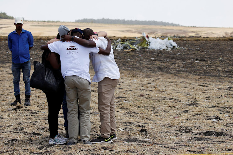 Kenyans mourn family and friends, who were victims of the Ethiopian Airlines Flight ET 302 plane crash, after a commemoration ceremony at the scene of the crash, near the town of Bishoftu, southeast of Addis Ababa, Ethiopia yesterday.