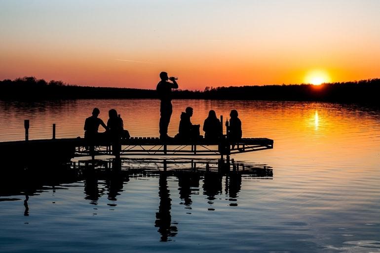 Silhueta de um grupo de pessoas observando o por do sol
