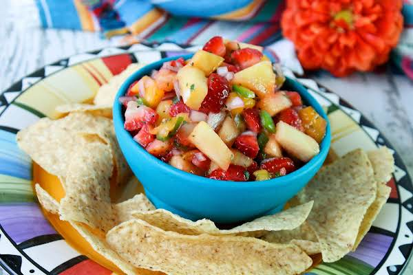 A Bowl Of Mango Strawberry Salsa With Tortilla Chips.