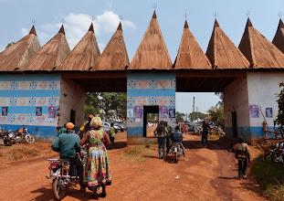 Photo: Eingangstor zum Palastbereich der Chefferie (Königreich) Baleng. Typisch für die Bauweise der Bamileke-Ethnie im Kameruner Grasland sind die Spitzkegeldächer. Je größer die Anzahl der Kegel desto größer die Bedeutung.
