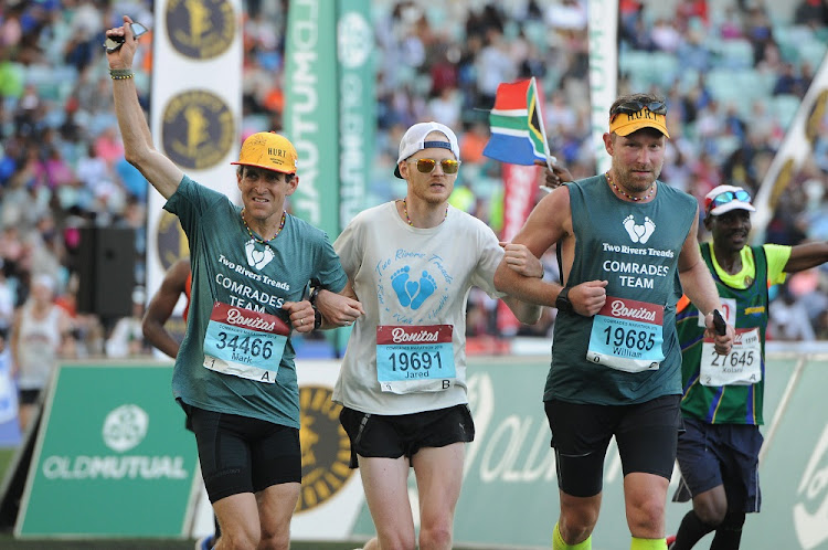 Dr Mark Cucuzella, far left, running the Comrades marathon. Under his t-shirt is a belt that carries his flask and an electrolyte product. Picture: SUPPLIED