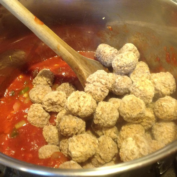 Add in the crushed tomatoes, tomato paste, diced tomatoes, and frozen meat balls. Allow...