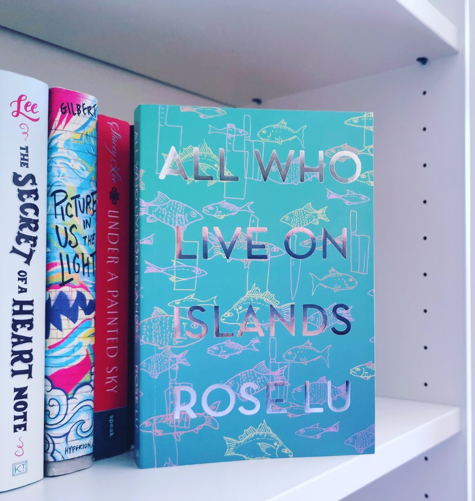 Photo of All Who Live on Islands on bookshelf, next to Under a Painted Sky, Picture Us in the Light, and Secret of a Heart Note