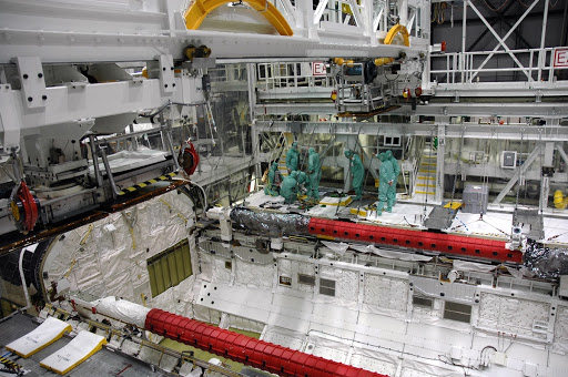 Workers prepare to install a camera pack on the orbiter boom sensor system in space shuttle Endeavour's payload bay.