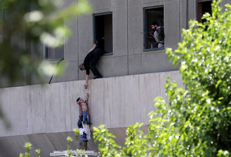 A child is evacuated during the attack on the Iranian parliament in central Tehran, Iran, on Wednesday. Picture: TASNIM NEWS/REUTERS