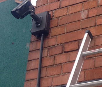 a black security camera having just been installed on a facebrick wall