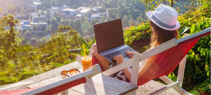 A person sitting on a deck with a computer and a cup of coffee  Description automatically generated with low confidence