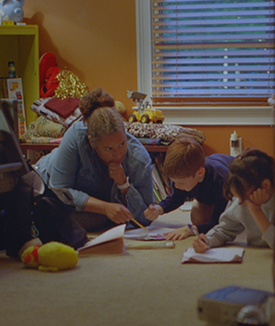 woman sitting with two children helping with homework
