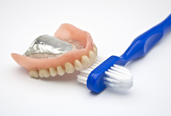 Dentures with a two-sided toothbrush