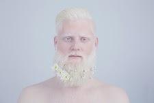 blanke man met witte haren en baard waarin witte bloemetjes zijn gestoken