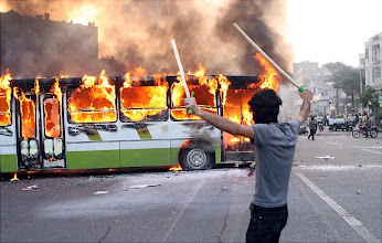 Photo: An Iranian protester stands next to a burning bus during clashes with Iranian police at a demonstration in Tehran on June 20, 2009. Thousands of Iranians clashed with police as they defied an ultimatum from supreme leader Ayatollah Ali Khamenei for an end to protests over last week's disputed presidential election. AFP PHOTO/ALI SAFARI (Photo credit should read ALI SAFARI/AFP/Getty Images)   Original Filename: DV_To_Getty_2830998_0.jpg