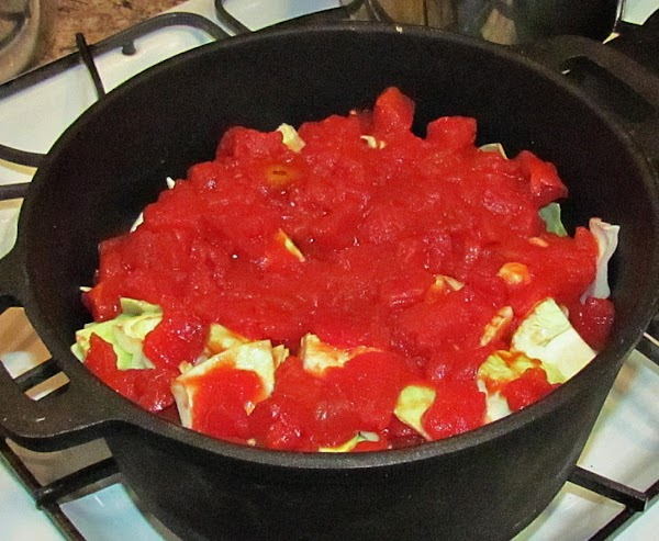 Pour crushed tomatoes over the cabbage and spread evenly.