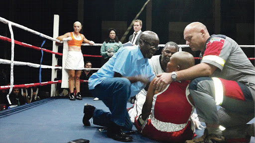 Doctor Solly Skosana, trainer Stanley Ndlovu and a paramedic attend to stricken boxer Phindile Mwelase before rushing her to hospital. She was caught by a right-handed punch to the head during a bout in Pretoria. Her opponent, Liz Butler, is in her corner