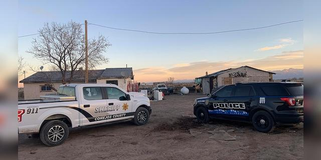 In this photo released by the Colorado Bureau of Investigation, law enforcement vehicles are parked at one of two properties where skeletal remains were found about 20 miles south-southeast of Alamosa, Colo., on Wednesday, Nov. 18, 2020. (Colorado Bureau of Investigation via AP)