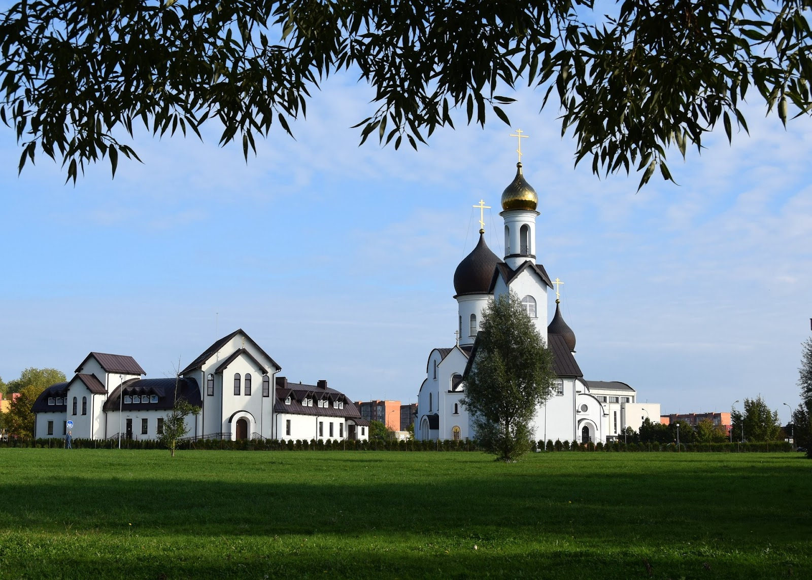 white church in klaipeda, lithuania. beautiful architecture, church is surrounded by green grass and trees lurking into the frame. sunny day.
