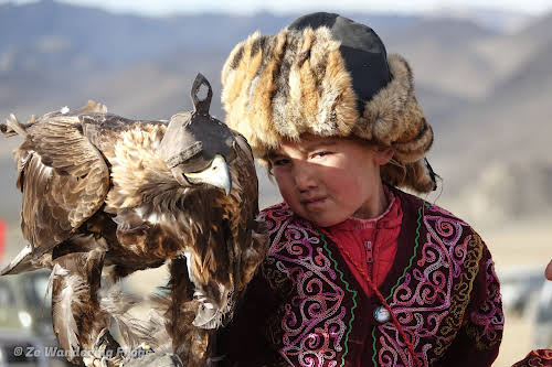 Mongolia. Golden Eagle Festival Olgii. One of the youngest girls with her eagle