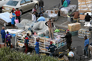 Foreign nationals pack trailers with goods to send home at a garage in Parktown, Johannesburg./ALON SKUY